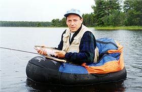 Fisherman in a float tube on Anahim Lake holding a nice rainbow trout..