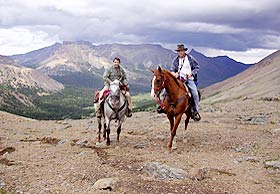 Two men on horses in the mountains.