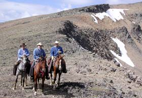 Three men on horses above a talus slope.