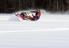 Snowmobile rider cutting curves.