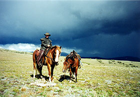 Horseback rider with storm clouds.